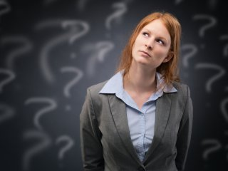 A young businesswoman thinks about a difficult problem or choice, surrounded by handwritten question marks.